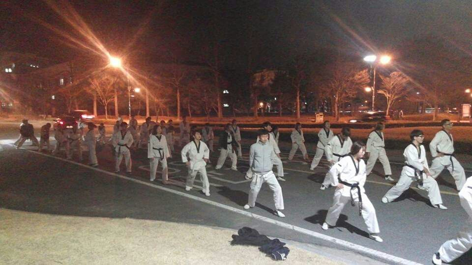 White taekwondo uniforms in front of Samgak garden